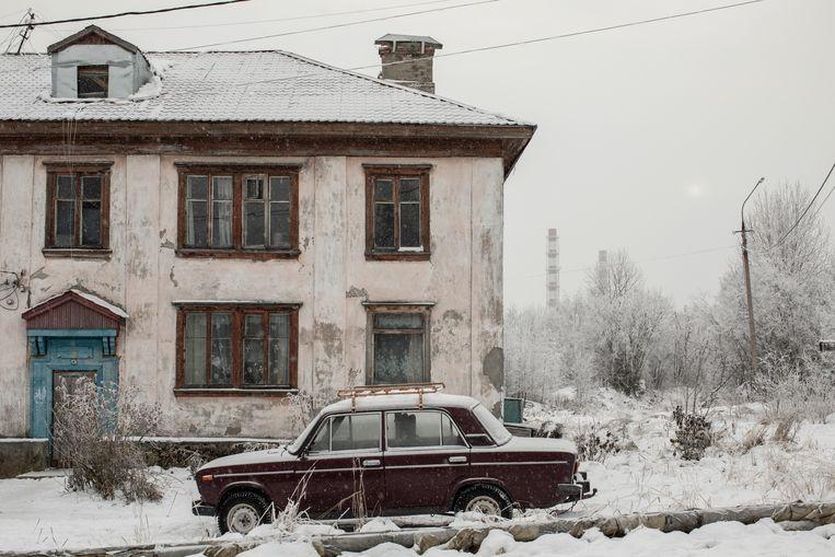 Een vervallen pand in Nadvoitsy, met de aluminiumfabriek in de achtertuin. Beeld Emile Ducke