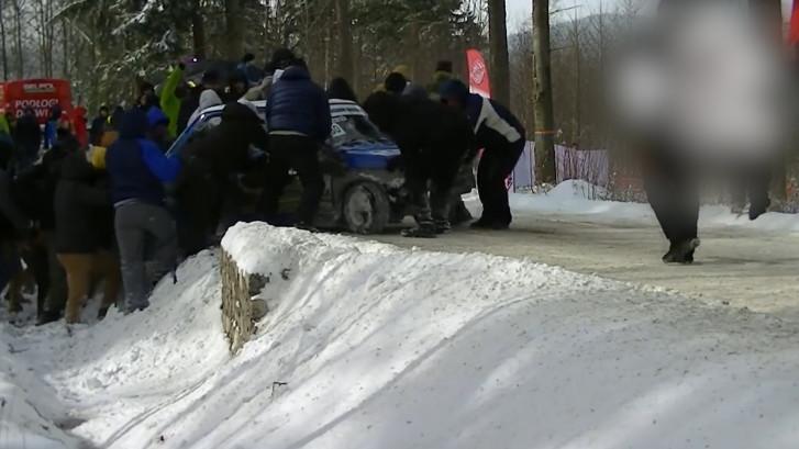 Toeschouwers tillen gecrashte racewagen uit greppel