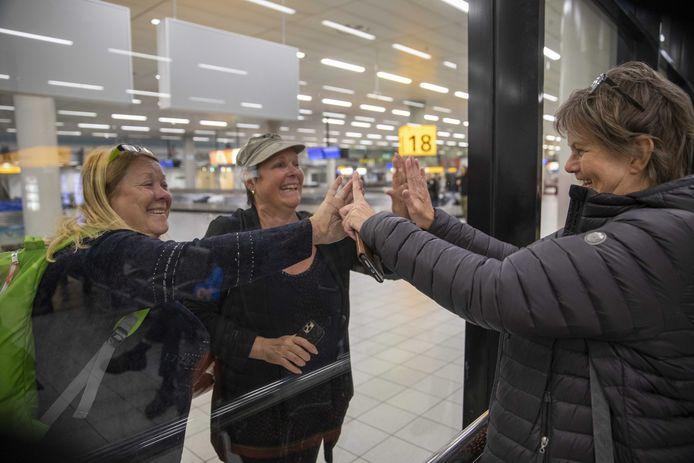 Passagiers begroeten familieleden door de glazen wand.