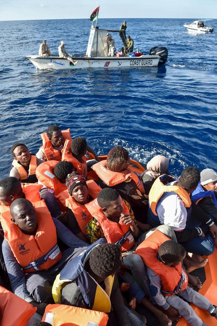 De Libische kustwacht helpt migranten aan boord van een reddingsschip. Beeld afp