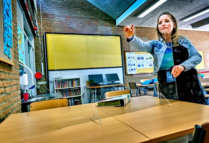 Locatieleidster Berber Wijnbelt plaatst het plexiglas op de bureaus waar de leerkracht kan overleggen met de leerlingen.