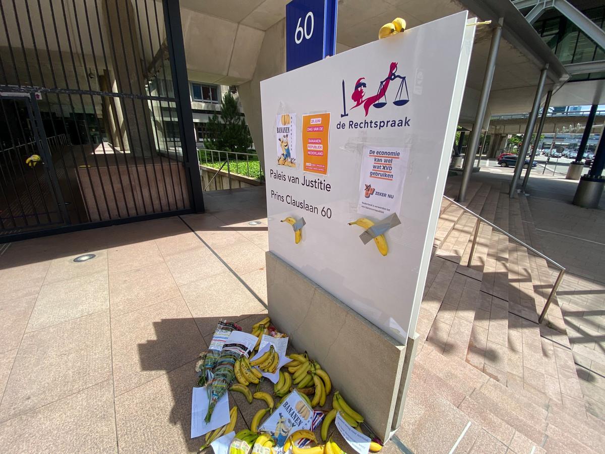 Met ducttape zijn ook velletjes papier met protestleuzen op het bord bij de Haagse rechtbank geplakt.