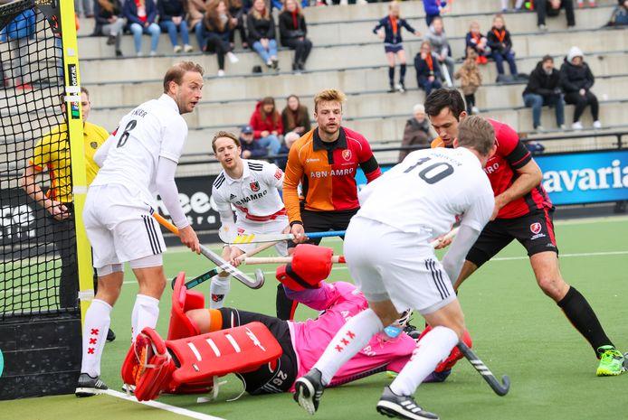 Mink van den Weerden en Niek van der Schoot van Oranje-Rood kijken toe hoe Pirmin Blaak voorkomt dat  Amsterdam kan scoren.