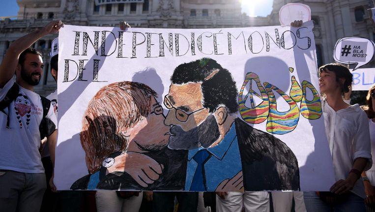 Demonstranten houden een tekening omhoog van een zoenende Catalaanse premier Carles Puigdemont en Spaanse premier Mariano Rajoy. Beeld afp