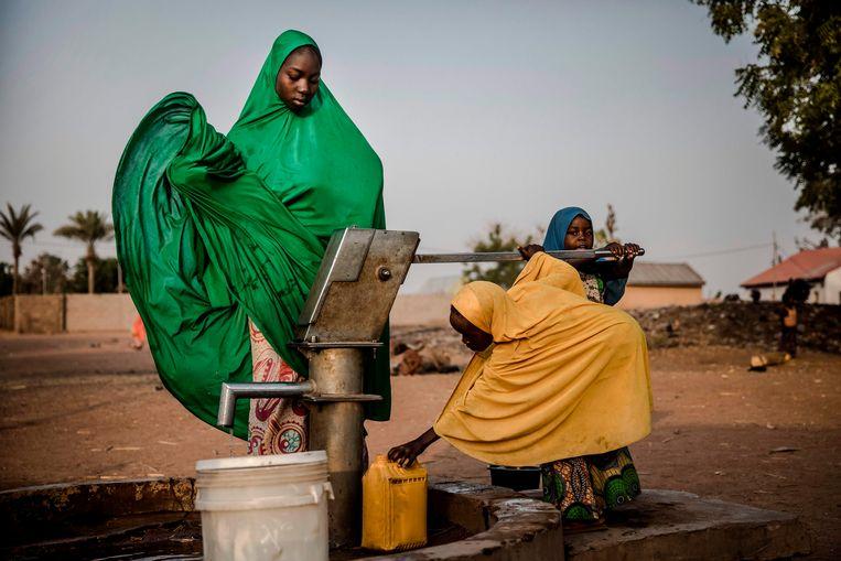 Vrouwen bij de dorpspomp in Nigeria, in een kamp voor bewoners die gevlucht zijn voor Boko Haram.  Beeld LUIS TATO/AFP