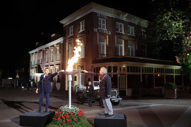 Staatssecretaris Paul Blokhuis (links) en de burgemeester van Wageningen Geert van Rumund ontsteken maandagavond het vrijheidsvuur bij Hotel De Wereld. Beeld ANP