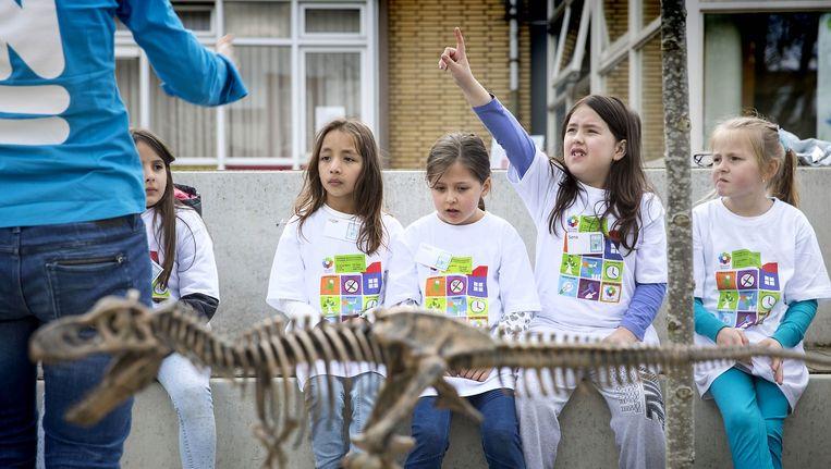 Kinderen van basisschool De Piramide krijgen les op het schoolplein. Beeld Werry Crone