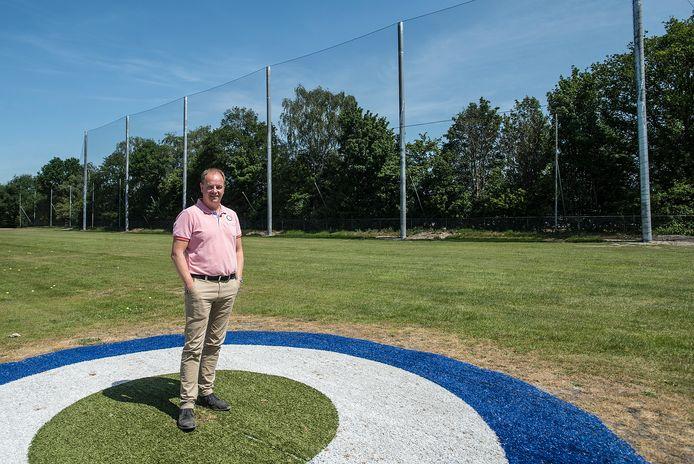 Martijn Kools bij 16 meter hoog hek dat geplaatst is tussen zijn bedrijf en de golfbaan van de Oosterhoutse golfclub.