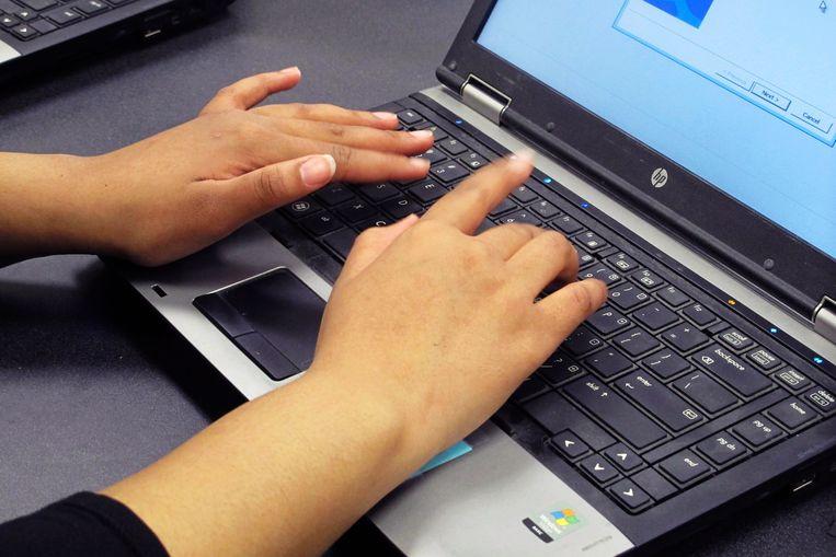 Een leerling gebruikt een laptop op school.