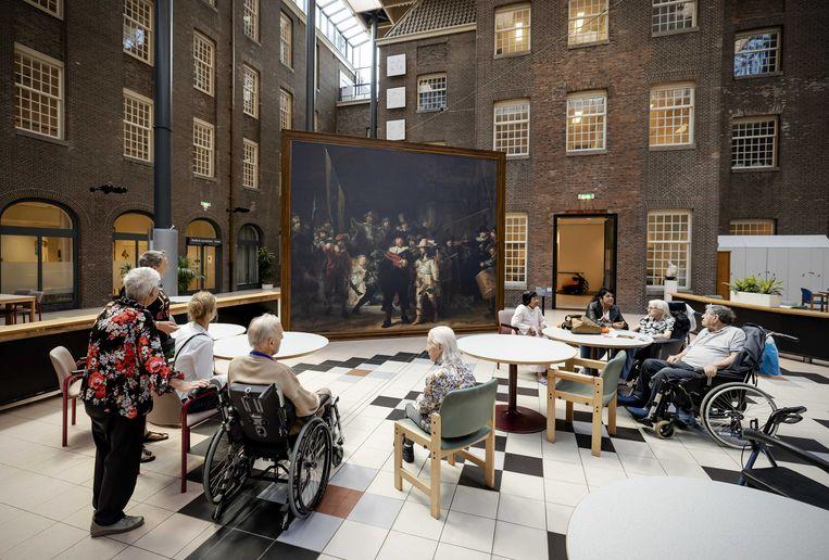 Bewoners van verpleeghuis Dr. Sarphatihuis in Amsterdam kijken naar een levensgrote Nachtwacht. Het Rijksmuseum brengt deze zomer een versie van het wereldberoemde schilderij van Rembrandt naar dertig verpleeg- en verzorgingshuizen en seniorencomplexen.  Beeld ANP