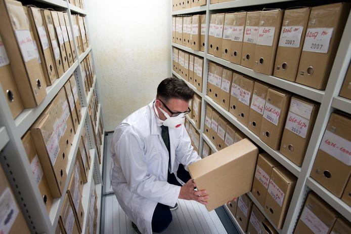 De dossiers en de wanden van het ondergronds archief op het gemeentehuis zijn aangetast door schimmel. Wethouder Mike Hofkens bekijkt de schade aan de dozen.