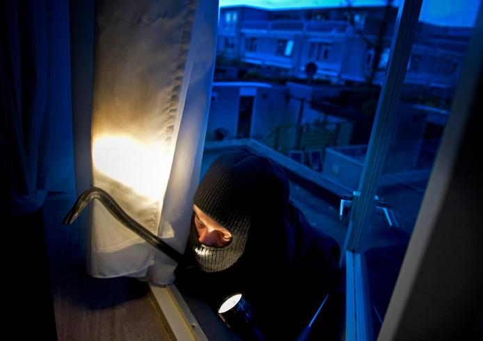 Een inbreker dringt een huis binnen (foto ter illustratie).