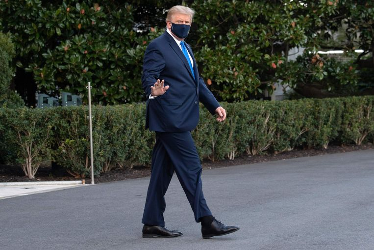 De met corona besmette Trump liep op eigen kracht naar de helikopter die hem naar het ziekenhuis vervoert. Hij wordt daar uit 'voorzorg' opgenomen. Beeld AFP