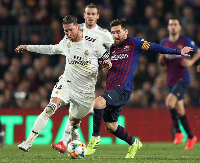 Lionel Messi in duel met Sergio Ramos (l).