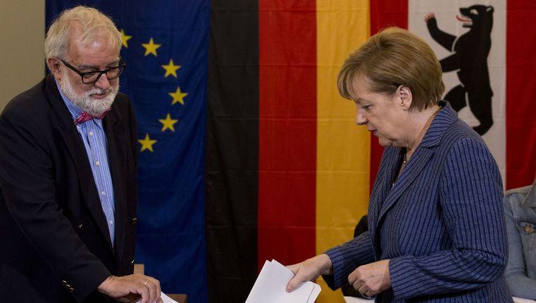 De Duitse bondskanselier Angela Merkel brengt haar stem uit in Berlijn. Beeld afp
