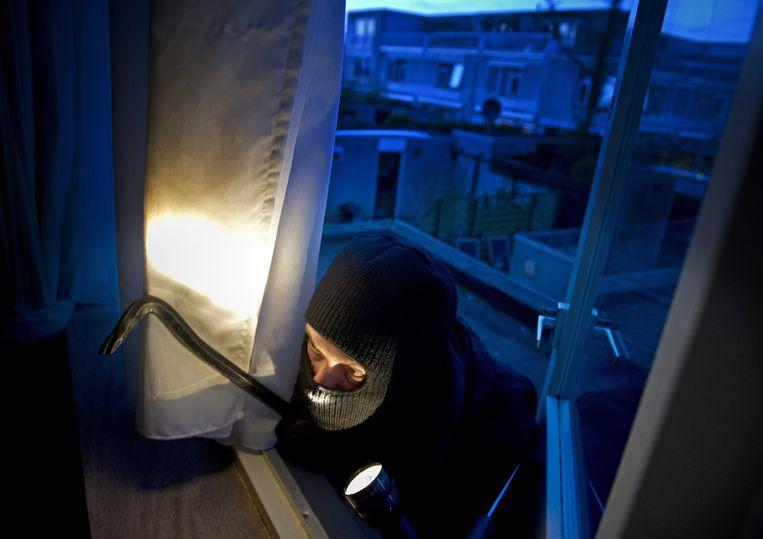 Een inbreker met breekijzer dringt een huis binnen. Beeld anp