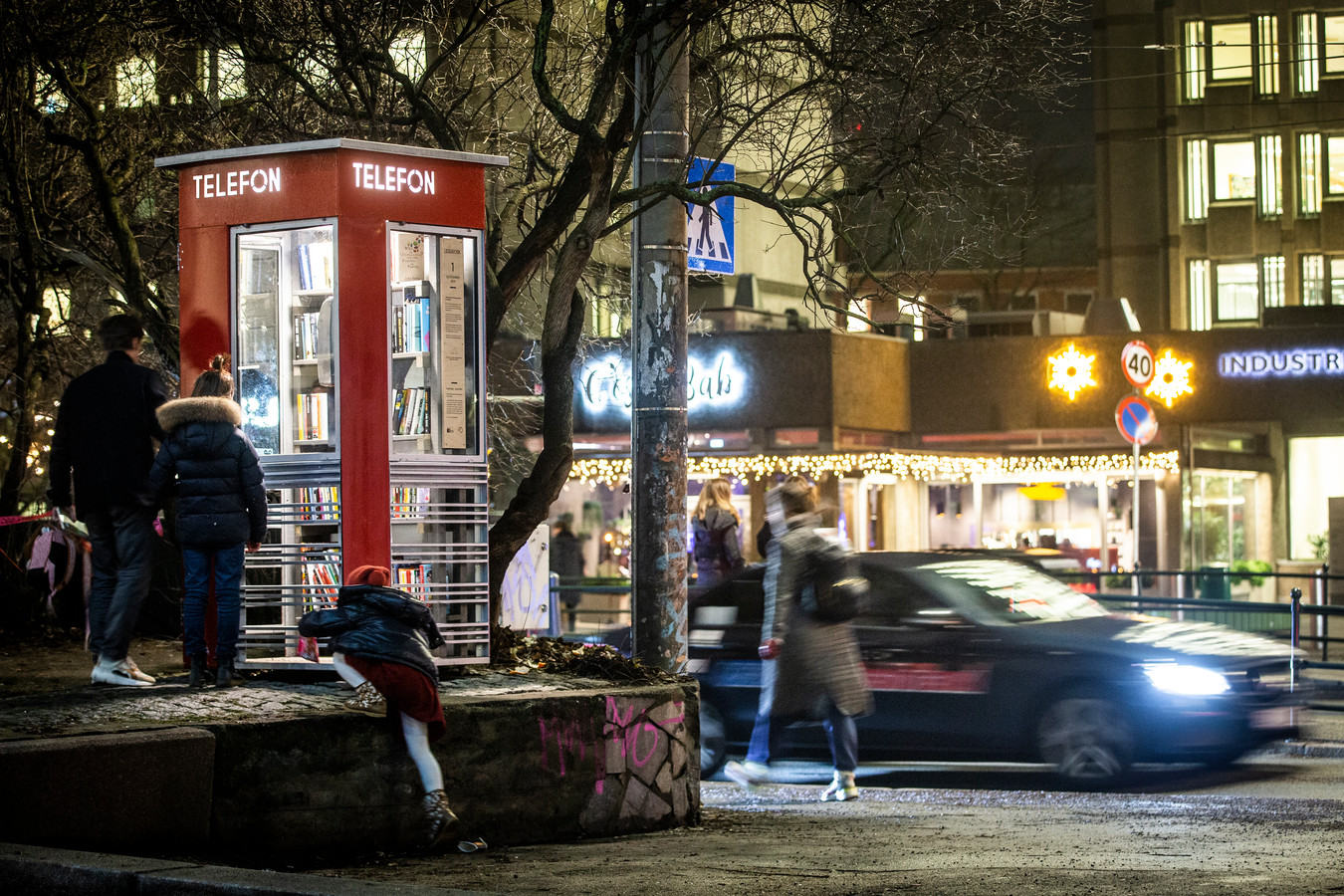 "People walk by a telephone kiosk, the first of 100 protected telephone kiosks in Norway to be converted into a reading kiosk, at Solli plass in Oslo, Friday, Dec. 13, 2019. It has been equipped with shelves and the principle is ""give a book, take a book"" (Trond Reidar Teigen/NTB scanpix via AP)"