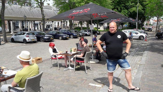 Koen Funk van Biercafe Damplein serveert met handschoentjes aan bier op parkeerplaats. Hij is blij met de medewerking van de gemeente Middelburg bij de heropening van de terrassen.
