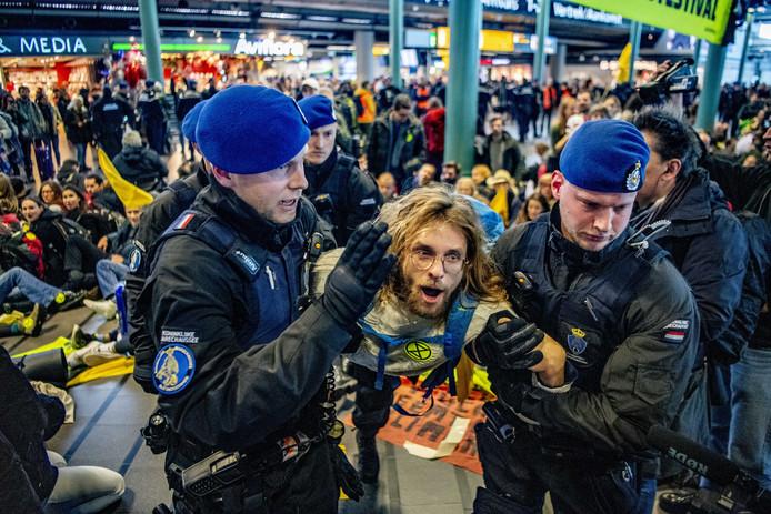 Actievoerders van Greenpeace worden door de Koninklijke Marechaussee afgevoerd op Schiphol.
