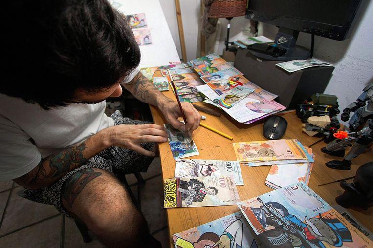 De Venezolaanse grafisch vormgever José Leon (26) beschildert bankbiljetten die niks meer waard zijn door hyperinflatie. Beeld AFP