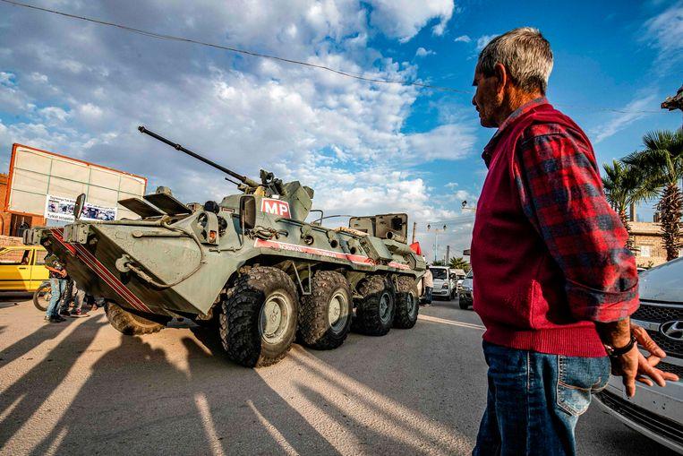 Een man kijkt toe terwijl een gepantserd Russisch militair voertuig door de straten van Amuda rijdt. Beeld null