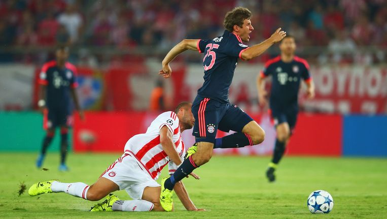 Thomas Mueller van Bayern München wordt onderuit gehaald door Pajtim Kasami van Olympiakos. Beeld getty