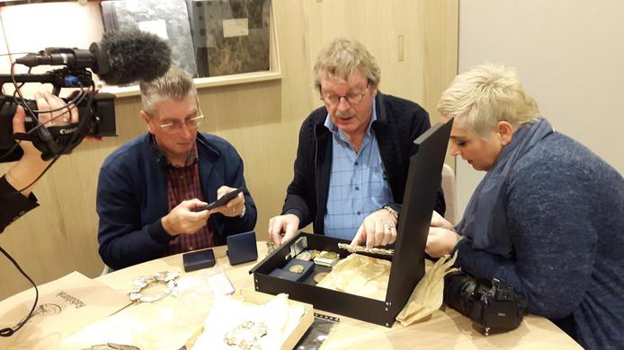 Terwijl de media toekijken, onderwerpen penningmeester Harry Mols, voorzitter Leo Wolfs en bestuurslid Judith Wientjens de collectie aan een eerste inspectie.