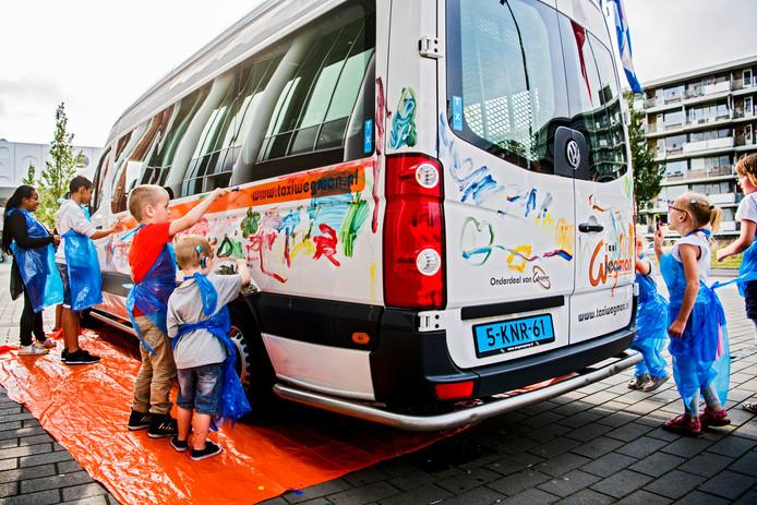 Archieffoto. Kinderen beschilderen een bus van taxibedrijf Wegman, toen dat leerlingenvervoerder werd in de Goudse regio.