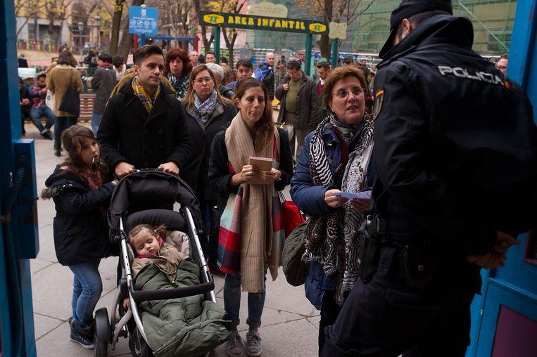Mensen staan in de rij in Madrid om hun stem uit te mogen brengen. Beeld getty
