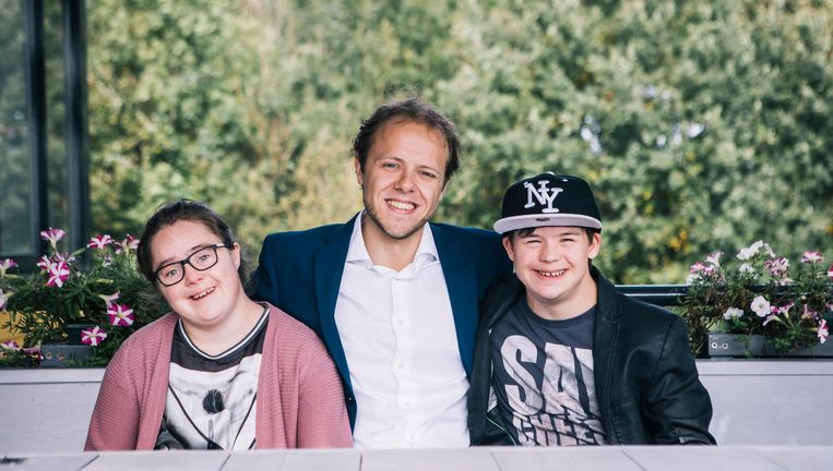 Dekker tussen twee jongeren met down, die werken in theehuis Zalkerveer van Dekkers ouders. Beeld Marcel Wogram