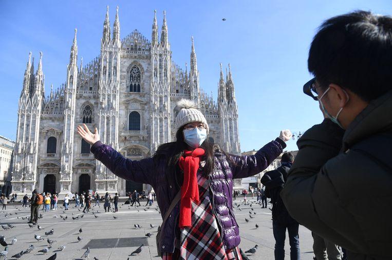 Een Taiwanese toerist draagt een mondkapje terwijl ze poseert voor de Kathedraal van Milan. Beeld EPA
