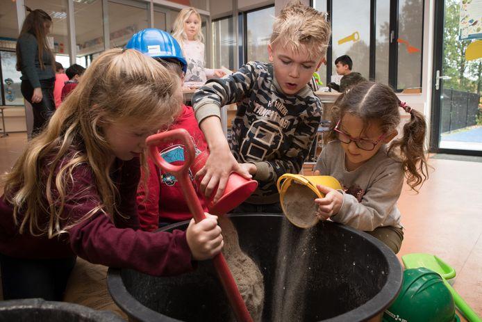 Leerlingen van de basisschool Kwintijn in Raalte kieperen zand in een cementbak om specie te maken.