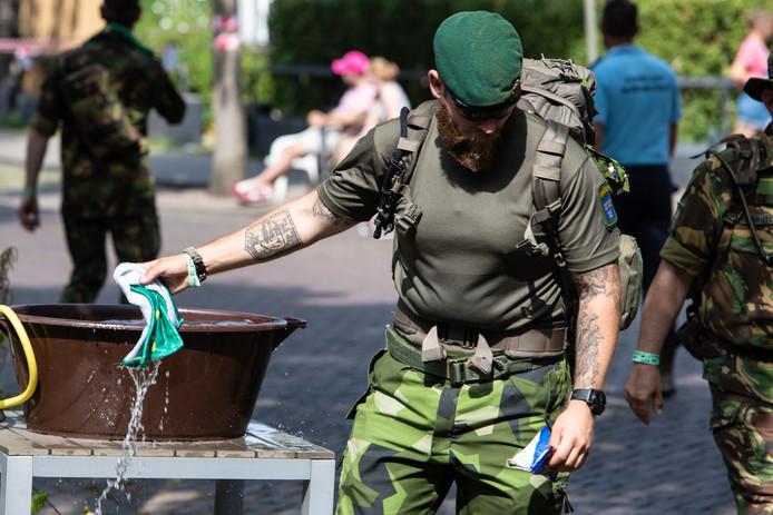 Deze militair zoekt verkoeling tijdens de tweede dag van de Vierdaagse.