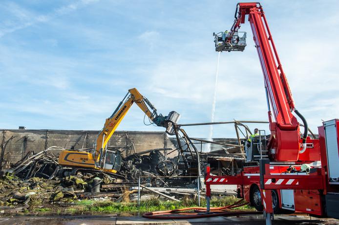 Het nablussen na de brand bij Tuf in Dongen op 11 oktober.