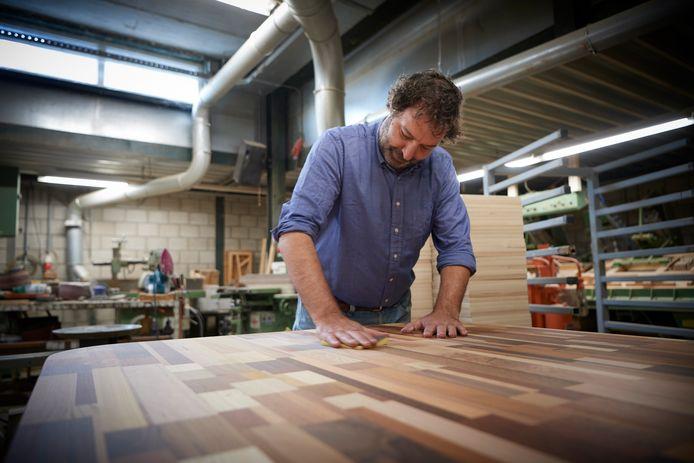 Rik Ruigrok schuurt een tafel tafel van zogeheten Brabants Bont - allerlei soorten en kleuren hout door elkaar.
