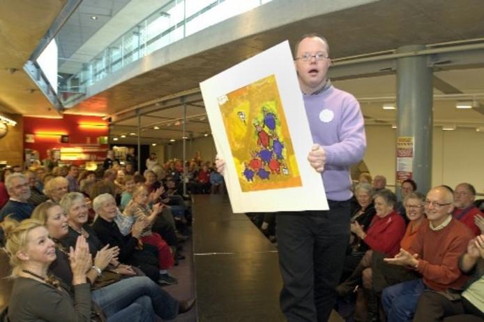 Bas Willems toont vol trots zijn schilderij, dat is geïnspireerd op aardappels. Willems tekende ze over en maakte er vrolijke mens-figuren van. Foto MAARTEN SPRANGH