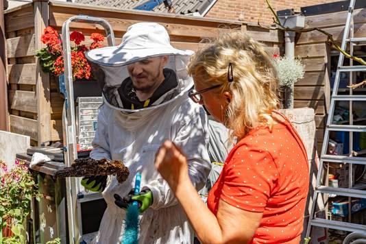 Imker Sejdi Sejdiu toont bewoonster Ingrid Linssen een stuk van de ongeveer 20 jaar oude honingraat met larven uit het bijennest in de schoorsteen van haar huis.