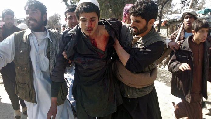 Een gewonde jongen wordt weggedragen van een protest tegen de koranverbranding.