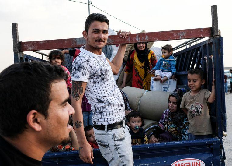 Een gezin uit de Syrische stad Qamishli arriveert in een vluchtelingenkamp in Badarash waar Syrische Koerden worden opgevangen die op de vlucht zijn voor de oprukkende Turken. Volgens de VN zijn daar inmiddels 7100 vluchtelingen aangekomen. Beeld Getty Images