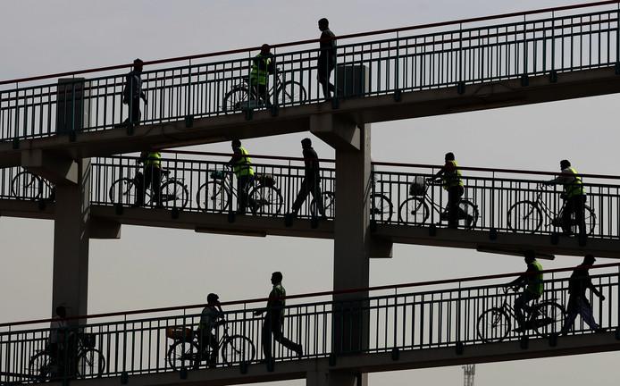 Aziatische arbeiders lopen over een voetgangersbrug in Dubai. Foto Karim Sahib