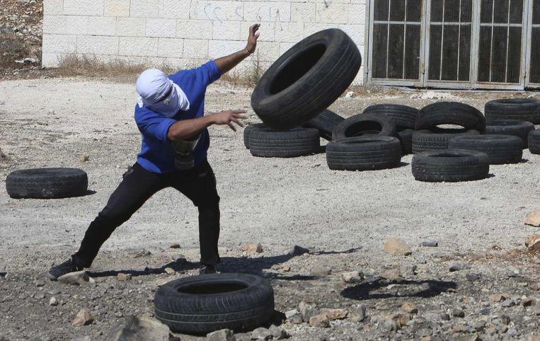 Een Palestijnse betoger gooit banden tijdens ongeregeldheden met Israëlische soldaten. Beeld reuters