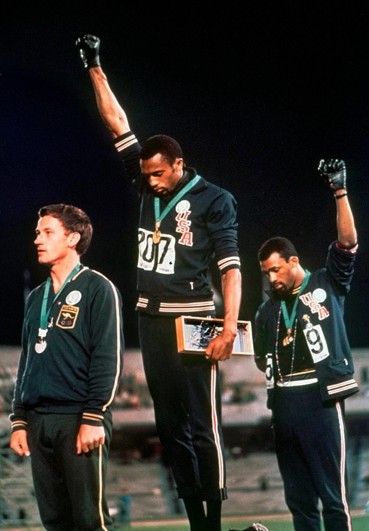 1968. De hoofden gebogen, de vuisten gebald. De Amerikaanse atleten Tommie Smith en John Carlos protesteren tijdens de Spelen van Mexico tegen het racisme in de VS. Beeld AP