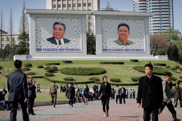Noord-Koreanen wandelen langs portretten van voormalige leiders Kim Il-sung en Kim Jong-un in een park in Pyongyang.