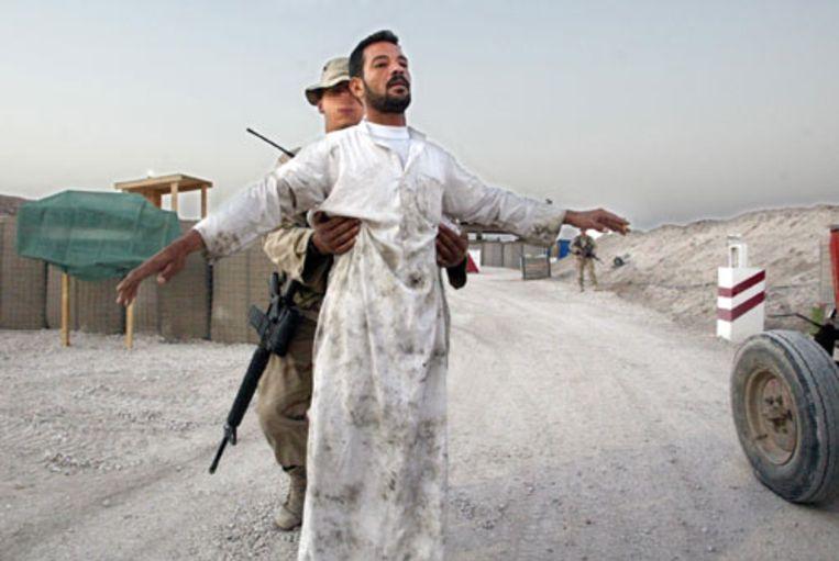Een Nederlandse militair fouilleert in september 2003 een Iraakse bezoeker van het kamp in As-Samawah, Zuid-Irak. Nederlandse officieren hebben in 2003 tientallen Iraakse gevangenen gemarteld in de Zuid-Iraakse provincie al-Muthanna. (ANP Archieffoto (25/09/2003)) Beeld