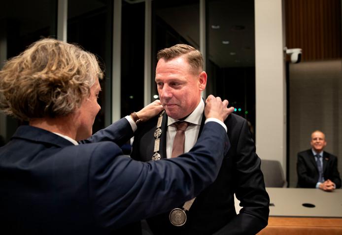 Wethouder Marc Jeucken hangt de kersverse burgemeester van Geldrop-Mierlo, Jos van Bree, zijn ambtsketen om.
