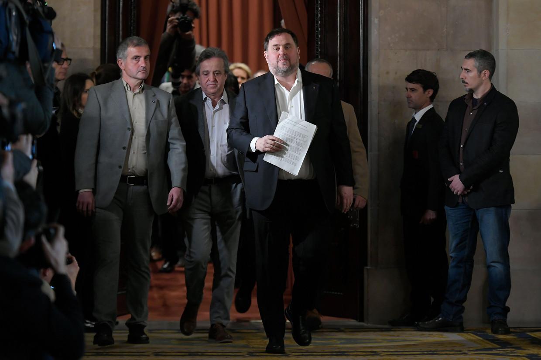 Oriol Junqueras (met papieren) verlaat eind januari een hoorzitting van een regionaal parlementair comité in Barcelona. Onder politie-escorte is hij met andere veroordeelde Catalaanse politici vanuit de gevangenis naar de bijeenkomst gebracht. Beeld Lluis Gene / AFP