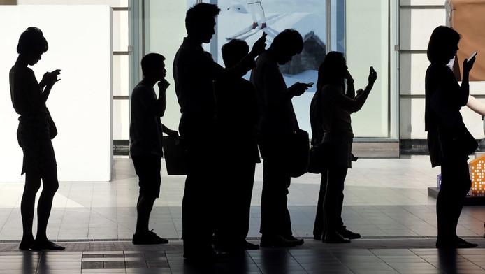 Mensen met mobiele telefoons.