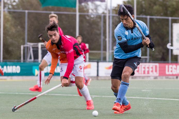 HGC'er Kenta Tanaka (rechts) haalt uit tegen Oranje-Rood.