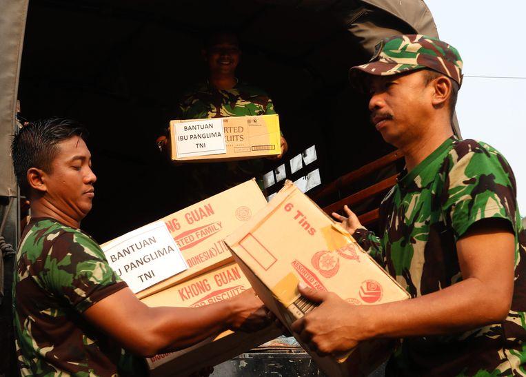 Leden van de Indonesische luchtmacht ontladen gedoneerde goederen die naar de getroffen gebieden in Sulawesi zullen worden gestuurd.