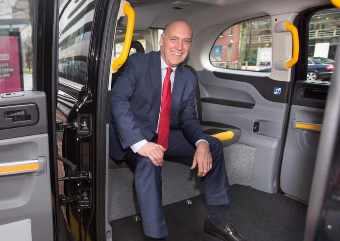 Wethouder De Bruijn in een nieuwe e-taxi, die lijkt op een Hackney of London taxi.
